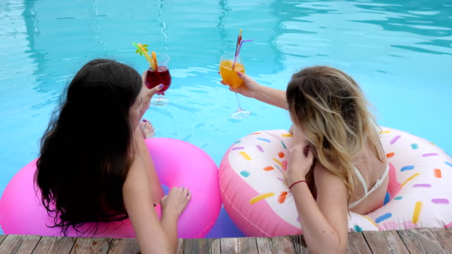 Expensive-holiday-Friends-on-inflatables-rings-resting-in-Poolside-Long-haired-girls-in-bathing-suits-relax-in-pool