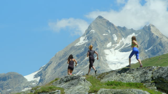 Three-women-run-up-a-high-altitude-mountain-range-