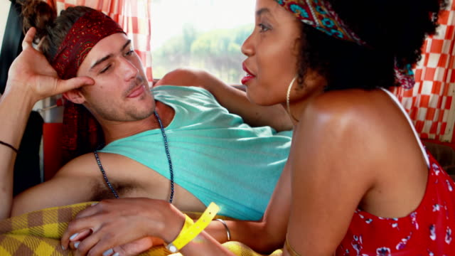 Couple-interacting-with-each-other-while-relaxing-in-camper-van-4k