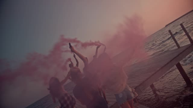 Multi-ethnic-friends-celebrating-with-smoke-bombs-on-jetty-at-sunset