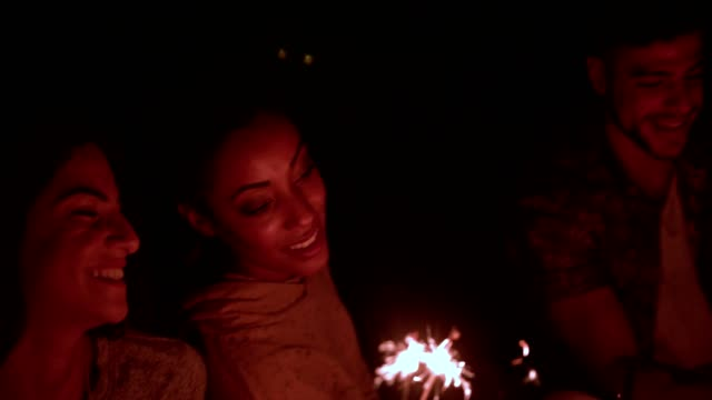 Young-multi-ethnic-hipster-friends-celebrating-with-sparklers-at-night