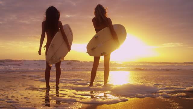 Chicas-de-Surfer-multi-étnico-usando-Bikinis-Sunrise-silueta