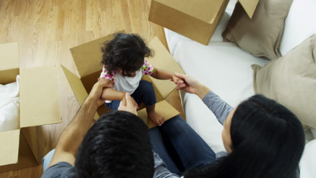 Young-Ethnic-family-new-home-playing-moving-cartons