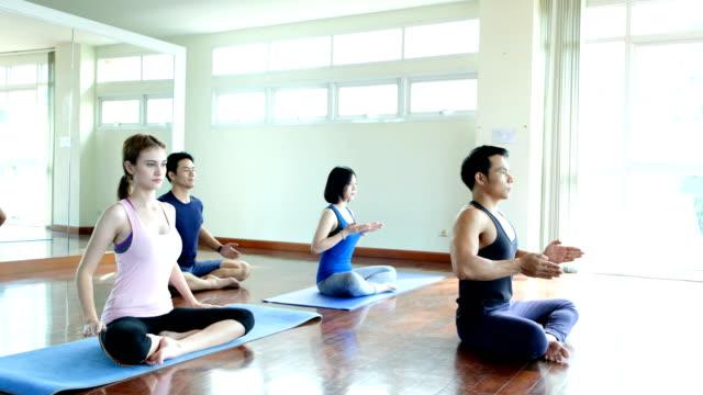 Grupo-de-jóvenes-haciendo-yoga-en-la-clase-