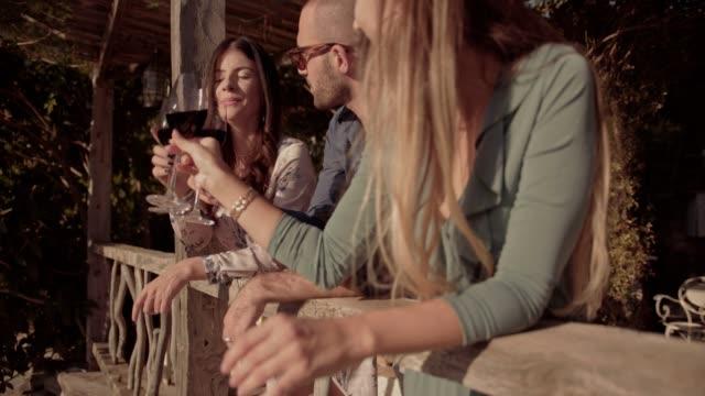 Elegante-Freunden-Toasten-mit-Rotwein-auf-rustikales-Landhaus-Balkon