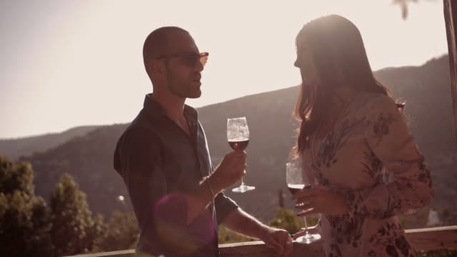 Young-couple-drinking-wine-on-rustic-balcony-with-mountain-view