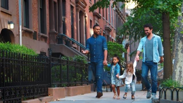 Zwei-Väter-und-ihre-Töchter-Fuß-in-der-Straße-reden