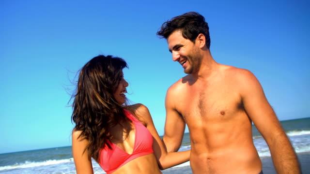 Portrait-of-multi-ethnic-couple-embracing-on-beach