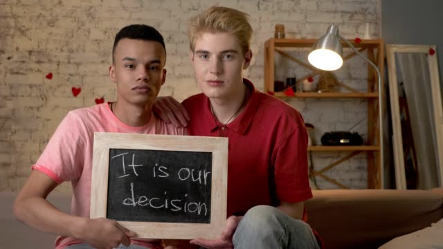 A-sad-international-gay-couple-is-sitting-on-the-couch-and-holding-a-sign-It-is-our-decision-Look-at-the-camera-Home-comfort-on-the-background-60-fps
