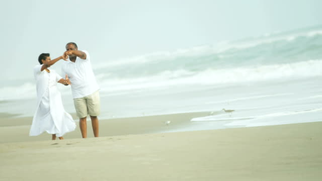 Retired-senior-ethnic-couple-dancing-together-on-beach