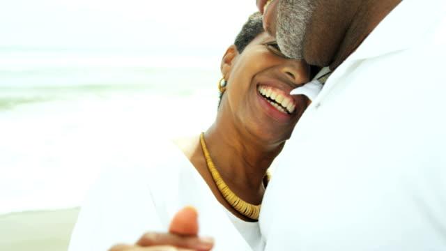 Retired-ethnic-couple-dancing-on-beach-enjoying-togetherness