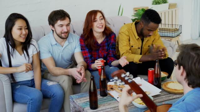 Amigos-jóvenes-felices-tengan-fiesta-piso-compartido-y-cantar-juntos-mientras-su-amigo-tocando-la-guitarra-en-casa