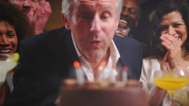 Group-Of-Middle-Aged-Friends-Celebrating-Birthday-In-Bar