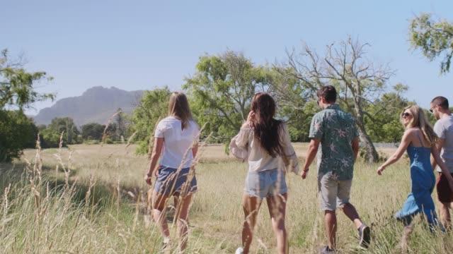 Carefree-friends-walking-in-open-field