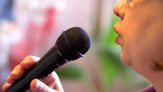 Senior-woman-signing-with-microphone-karaoke-in-slow-motion-4k-slow-motion