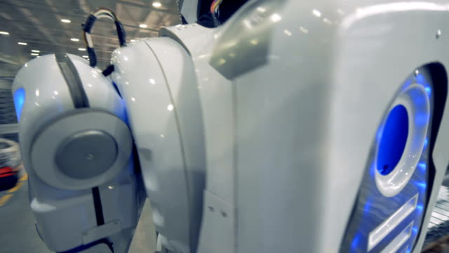 A-white-robot-carries-a-metal-item-at-a-factory-close-up-