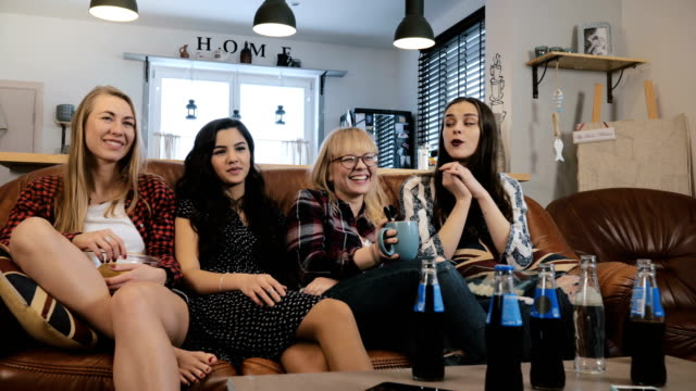 Pretty-girlfriends-watch-and-discuss-movie-on-TV-Happy-smiling-female-friends-enjoy-comedy-film-together-4K-slow-motion