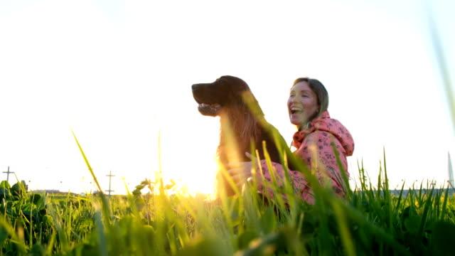 Mujer-abrazando-al-perro-al-atardecer-y-riendo-niña-con-mascota-sentados-sobre-la-hierba-y-descansar-en-la-naturaleza