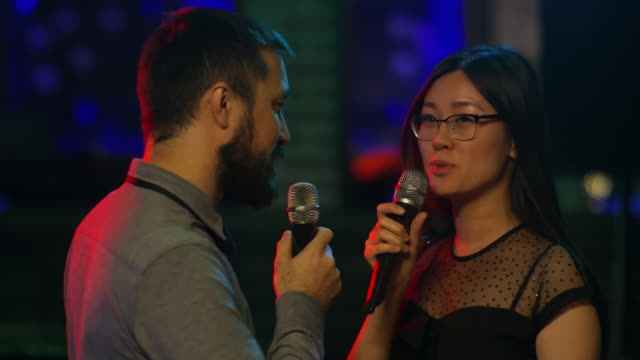 Asian-Friends-Singing-Karaoke-and-Smiling