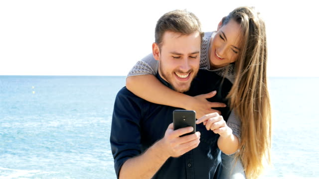 Happy-couple-joking-and-using-phone-on-the-beach