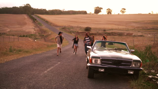 Teenager-friends-running-outside-at-sunset-to-their-car