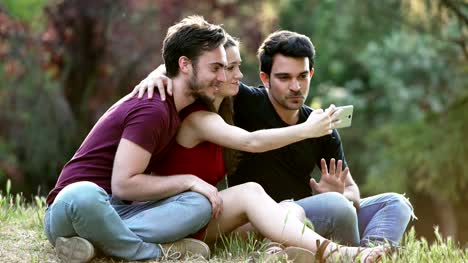 taking-selfie-at-the-park--three-young-friends-sitting-on-the-lawn-making-selfie