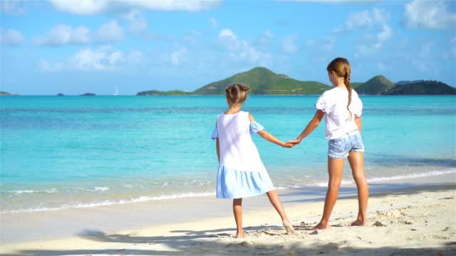 Niñas-graciosas-felizes-tienen-un-montón-de-diversión-en-playa-tropical-tocando-juntos-Día-soleado-con-lluvia-en-el-mar