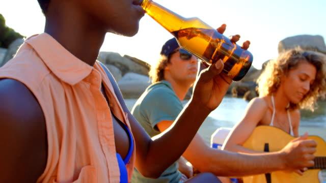 Group-of-friends-having-beer-in-the-beach-4k