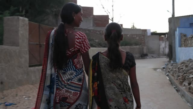Two-girls-walk-stroll-holding-hands-friends-bond-home-streets-rural-setting-happy-bonding-share-cute-outdoor-meet-follow-gimbal-behind-village-small-town-India-traditional-dress-costume-brick-wall