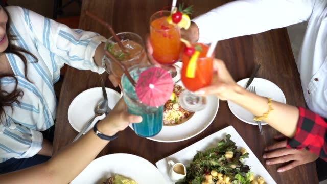 Top-view-of-Four-good-friends-toasting-saying-cheers-and-holding-tropical-cocktail-drinks-at-bar-and-restaurant