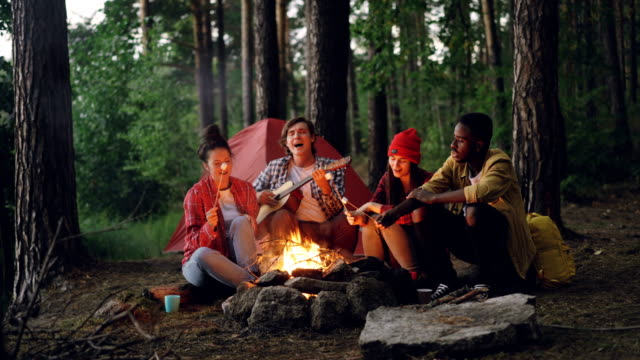 Tourist-is-playing-the-guitar-sitting-near-campfire-with-friends-singing-and-having-fun-young-people-are-holding-sticks-with-marshmallow-above-flame-Food-music-and-fun-concept-