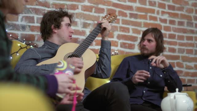 Dos-jóvenes-sentados-en-sofá-uno-tocando-la-guitarra