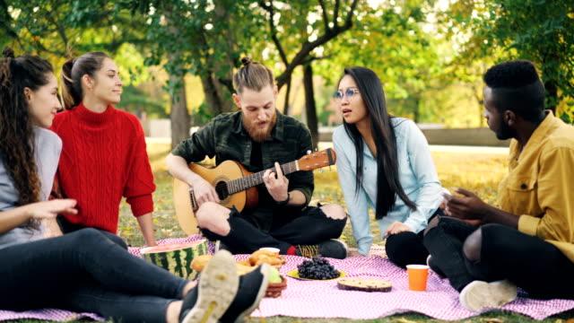 Chico-guapo-es-tocar-la-guitarra-mientras-su-hombre-y-amigas-escuchando-música-cantando-y-divirtiéndose-en-el-picnic-en-el-parque-Concepto-de-amistad-y-cultura-