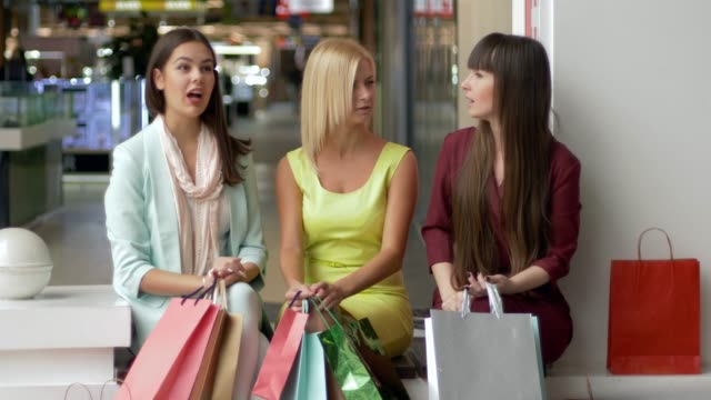 black-Friday-ladies-having-fun-discuss-their-purchases-together-while-sitting-at-mall-and-then-look-at-camera-and-smiling-with-paper-bags