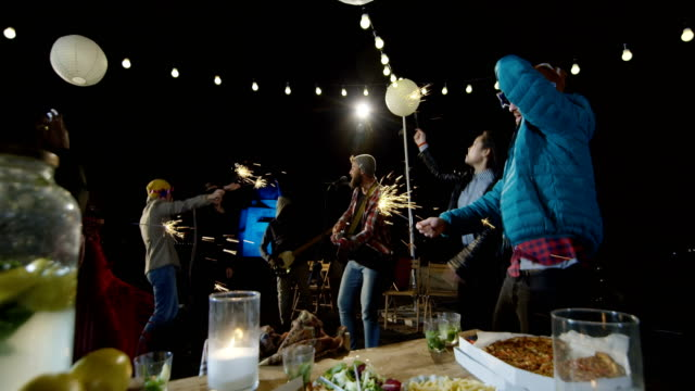 People-dancing-with-sparklers-on-a-rooftop