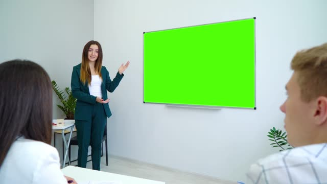 young-happy-teacher-near-with-a-green-screen-board-teaching-students-in-classroom