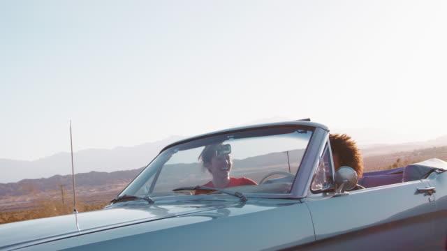 Lachend-Freundinnen-auf-einer-Autobahn-im-Cabrio-fahren