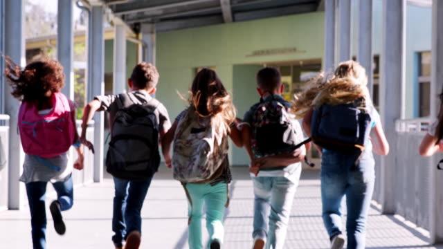 Elementary-school-kids-run-from-camera-in-school-corridor
