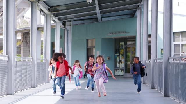 Niños-de-escuela-primaria-a-cámara-en-corredor-de-escuela