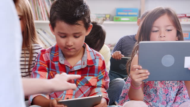 Lehrer-und-Kinder-in-einer-Grundschule-mit-Tabletten