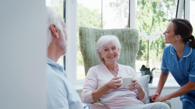 Senior-pareja-sentada-en-la-silla-y-hablando-con-la-enfermera-en-el-hogar-del-jubilado