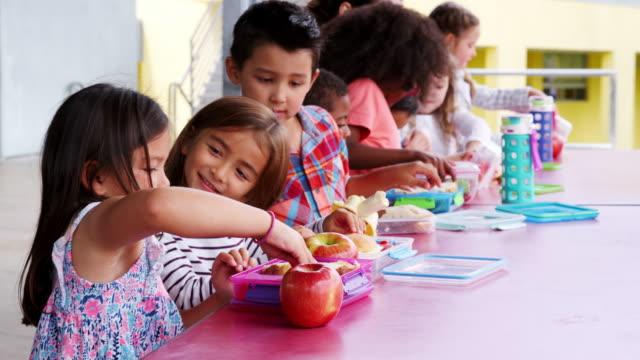 Escuela-primaria-los-niños-sentados-en-mesa-con-almuerzos