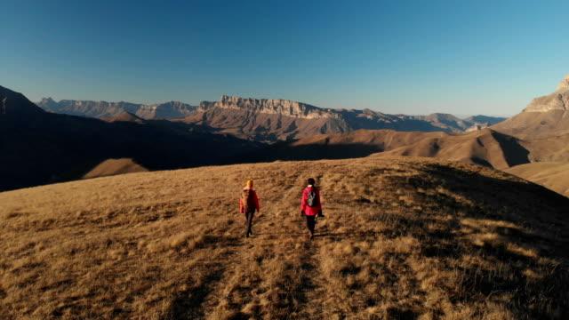 Vista-aérea-de-un-viajero-de-dos-chicas-con-mochilas-y-cámaras-de-pasear-por-las-colinas-entre-las-rocas-épicas-en-las-montañas-Fotógrafos-de-las-niñas-con-sus-cámaras-al-atardecer
