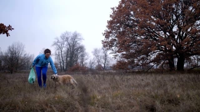 Mujer-ecología-con-perro-limpieza-de-basura-en-la-naturaleza