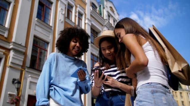 Niedlichen-Rassen-Mädchen-teilen-Smartphone-im-freien