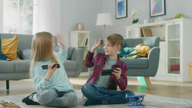 At-Home-Sitting-on-a-Carpet:-Cute-Little-Girl-and-Sweet-Boy-Playing-Togethe-in-Video-Game-on-two-Smartphones-Holding-them-in-Horizontal-Landscape-Mode-Happy-Children-do-High-Five-