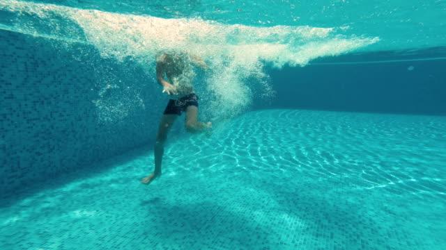 Divertido-niño-bajo-el-agua-en-la-piscina
