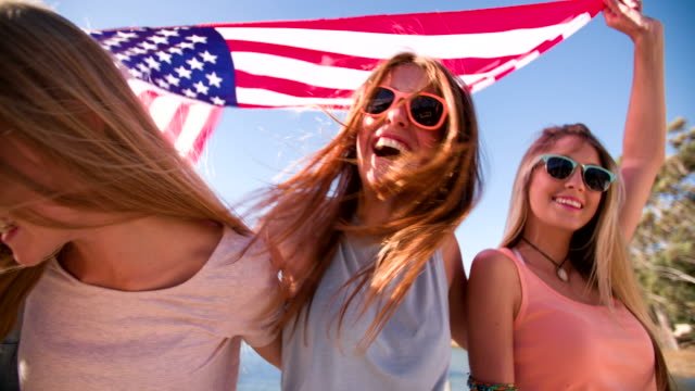 Cool-teen-friends-smiling-and-holding-an-American-flag