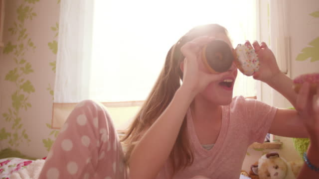 Girls-having-a-pyjama-party-with-sugary-donuts
