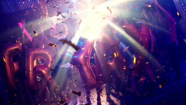 Group-of-friends-dancing-in-a-nightclub-holding-FRIYAY-balloons